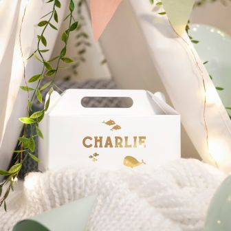 large white gable box with charlie written on the side with cartoons of dolphins, fishes and a whale printed in metallic gold