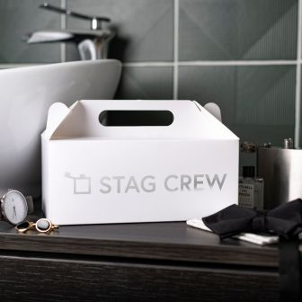 Large white gable box with an outline of a hipflask and the words stag crew in metallic silver vinyl on the side. The box is set in front of a sink and surrounded by a watch, cufflinks and bow tie