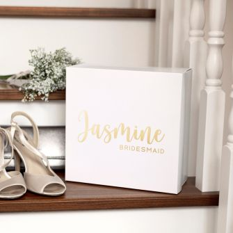 White square box with jasmine bridesmaid written on the front in metallic gold. The box is set on a staircase with flowers, wedding shoes and a clutch bag