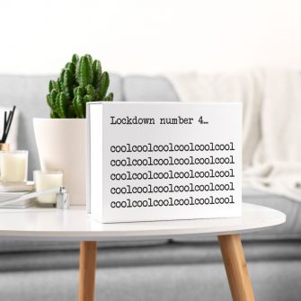 White magnetic gift box with the words Lockdown Number 4... is followed by Cool, repeated numerous times. It is black text on a white box. The box is set in a comfy lounge scene.