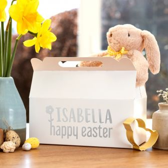 product lifestyle shot of a white gable box with silver metallic vinyl the background has daffodils and a cuddly toy bunny sitting inside the box
