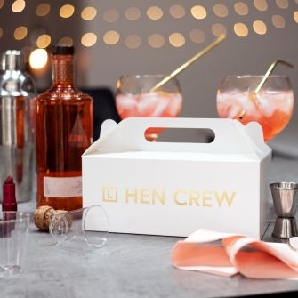 White gable box with L plate hen crew in metallic gold on the side. Set in front of cocktails and party themed decorations