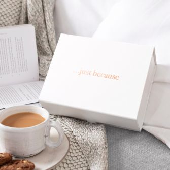 White magnetic gift box with metallic rose gold vinyl print that says '...just because'. The box is pictured on a sofa with a book, throw, and cup of tea.