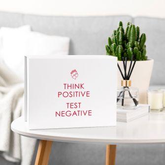 White magnetic gift box with an outline of The Queen's head wearing a face mask and the words 'Think Positive, Test Negative' in red underneath. The box is set in a living room setting.