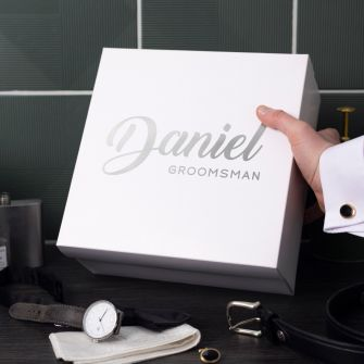 white square box with daniel groomsman written in metallic silver on the lid. The box is being placed by a groomsman onto a black surface that also holds a watch, belt, cufflink and tie
